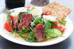 Bacon Arugula Salad. Arugula lettuce, bacon, parmesan cheese salad. Spiced with black pepper and olive oil. Gluten free crispbread royalty free stock photo