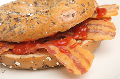 Bacon Bagel Breakfast Roll. Seeded bagel roll with crispy streaky bacon and tomato ketchup Stock Images