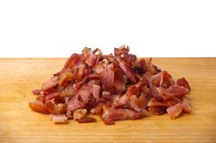 Bacon bits. Cooked bacon bits on wooden chopping  board Stock Photo