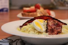 Bacon Boiled Egg Cabbage Salad for Breakfast with Baked Bread and Strawberries stock image