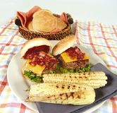 Bacon burger. Bacon and cheese hamburger with corn on the cob stock photography