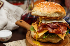 Bacon burger with beef patty and egg on wooden table stock image