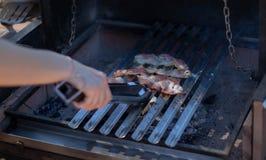 Bacon che cucina sul barbecue del carbone con le mani che tengono un paio delle tenaglie immagine stock libera da diritti