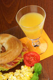 Bacon and cheese bagel with scrambled eggs and juice Royalty Free Stock Photo