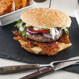 Bacon cheese bbq burger on wooden table with fries Royalty Free Stock Images