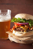 Bacon cheese burger with beef patty tomato onion beer.  Stock Photos