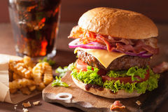 Bacon cheese burger with beef patty tomato onion cola.  Stock Photos