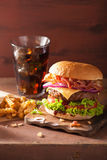 Bacon cheese burger with beef patty tomato onion cola Stock Image