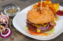 Bacon cheese burger with beef patty tomato onion and potato chips. On table Royalty Free Stock Photo