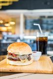 Bacon cheese burger with beef on wood board in restaurant. Unhealthy food style Royalty Free Stock Images