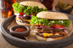 Bacon cheese burger with pickles tomato onion Royalty Free Stock Images