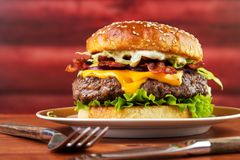 Bacon cheese burger. On plate with homemade brioche bun , red wooden log background royalty free stock photography