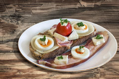 Sandwich With Bacon Rashers And Egg Cheese Ham And Cherry Tomato Served in Porcelain Plate Set On Old Cracked Flaky Picnic Table Stock Photos