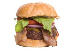 Bacon Cheeseburger. Big Bacon Cheeseburger with lettuce, red onion and tomato on a sesame seed bun royalty free stock photos