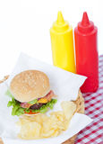 Bacon Cheeseburger in a basket. Bacon Cheeseburger and chips  in a basket with a checkered tablecloth and ketchup and mustard bottles Stock Photography