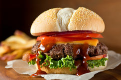 Bacon Cheeseburger. A delicious messy homemade bacon cheeseburger with barbecue sauce, lettuce, tomato, and onion stock photos