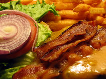 Bacon Cheeseburger and French Fries. This is a close up image of a bacon cheeseburger and french fries royalty free stock image