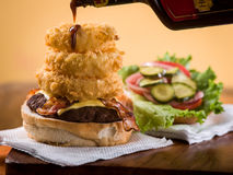 Bacon cheeseburger with stack of onion rings. Drizzled with barbecue sauce sitting on napkin on wooden table Royalty Free Stock Images