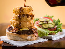 Bacon cheeseburger with stack of onion rings. Drizzled with barbecue sauce sitting on napkin on wooden table Stock Image