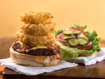 Bacon cheeseburger with stack of onion rings. On napkin on wooden table Royalty Free Stock Photography