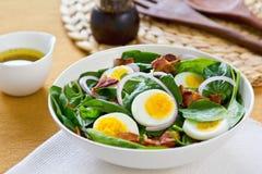 Bacon con l'insalata degli spinaci e dell'uovo fotografia stock
