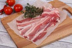 Bacon crudo sul bordo immagine stock libera da diritti
