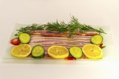 Bacon cut into thin slices with dill and cucumber and with Lemon. royalty free stock image