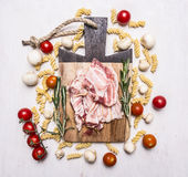 Bacon on a cutting board, around lie ingredients for cooking fusilli pasta on wooden rustic background top view close up Stock Photos