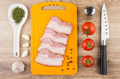 Bacon on cutting board. Tomatoes, garlic, greens and knife Stock Photos