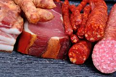 Bacon with dried sausages, prosciutto and salami. On table Stock Photos