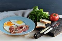 Bacon e ovos em uma placa azul, brinde Fotografia de Stock Royalty Free