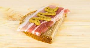 Bacon e senape sul pane di segale su un bordo di legno Fotografie Stock