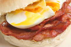 Bacon & Egg Bap or Roll. Soft white bap with streaky bacon and poached eggs Royalty Free Stock Images