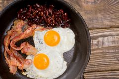 Bacon,Egg and bean. Salted egg and sprinkled with black pepper. English breakfast. Grilled bacon, two eggs and beans in pan on woo Royalty Free Stock Image