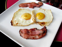 Bacon and egg breakfast. Hot morning breakfast of fried eggs and bacon on a white plate Royalty Free Stock Photography