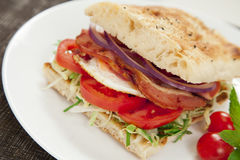 Bacon and egg burger. Healthy bacon and egg burger with onions, tomatoes and lettuce on turkish bread Royalty Free Stock Photos