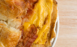 Bacon egg and cheese croissant breakfast sandwich on plate close Royalty Free Stock Image