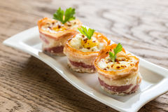 Bacon egg cups. Decorated with parsley leaves on the plate Stock Photography