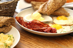 Bacon and eggs. Breakfast of bacon and eggs with sunny side up, brown bread and pat of butter Stock Images