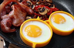 Bacon and Eggs. Cooking in a pan, with sauteed mushrooms Royalty Free Stock Image