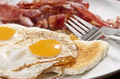 Bacon and eggs. On toast served on white plate stock images
