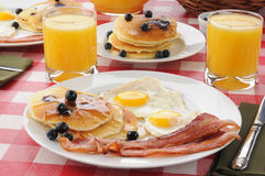 Bacon and eggs with blueberry pancakes. A breakfast with bacon and fried eggs with blueberry pancakes and orange juice Royalty Free Stock Photography