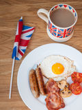 Bacon and eggs with cup of tea and british flag. Full cooked English Break fast on a wooden table with cup of tea  and british flag Royalty Free Stock Images