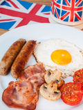 Bacon and eggs with cup of tea and british flag behind. Close-up of cooked English breakfast on a wooden table with cup of tea  and union jack flag behind in Royalty Free Stock Photography