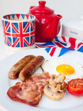 Bacon and eggs with cup of tea and british flag behind. English fried breakfast on a white table top with cup of tea in union jack mug, teapot  and british flag Stock Photo