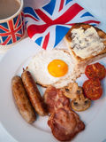 Bacon and eggs with cup of tea, toast and british flag behind. English fried breakfast on a white table top with cup of tea in union jack mug, buttered toast Stock Image