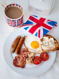 Bacon and eggs with cup of tea, toast and british flag behind Stock Photos