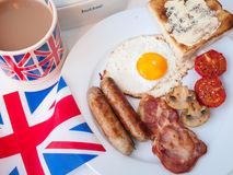 Bacon and eggs with cup of tea, toast and british flag. Full cooked english breakfast on a white table top with cup of tea in union jack mug, butter dish Stock Photography