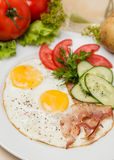 Bacon and eggs with garnish on white plate Royalty Free Stock Photography