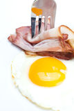 Bacon with eggs on a plate, fork and bread Stock Images